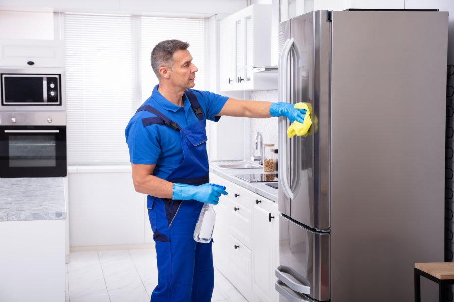 Male Janitor Cleaning Refrigerator With Yellow Napkin And Spray Detergent
